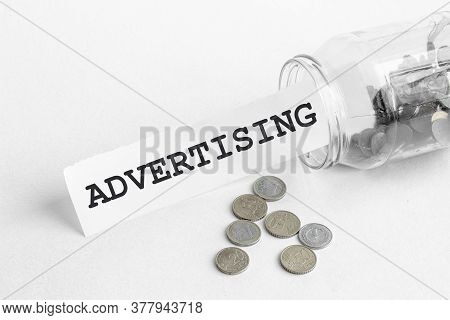 Sticking Out Of A Jar Of Coins A Piece Of Paper With A Text Advertising On A White Background