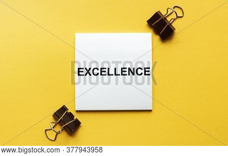 White Paper With Text Excellence On A Yellow Background With Stationery