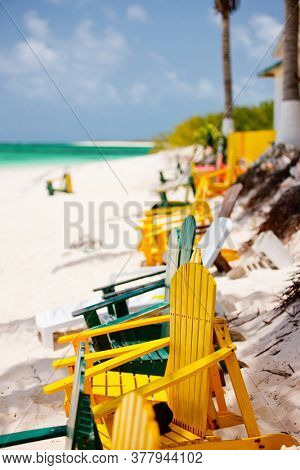 Colorful wooden chairs on tropical beach of Anegada island in Caribbean with beautiful turquoise ocean water, white sand and blue sky