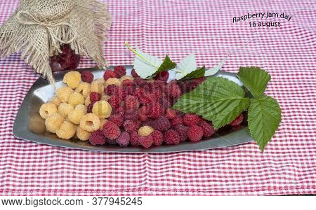 There Is A Tray Of Yellow And Red Raspberries On A Napkin. On Top Are Raspberry Leaves. A Jar Of Ras