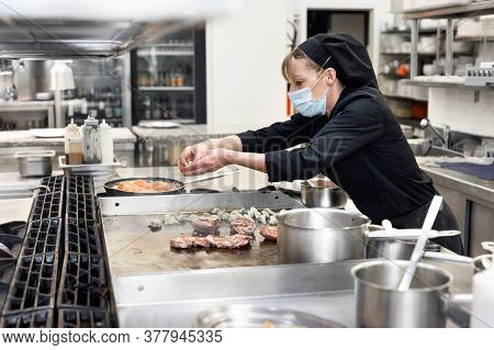 Chef In Uniform Cooking In A Commercial Kitchen. Female Cook Wearing Apron Standing By Kitchen Count