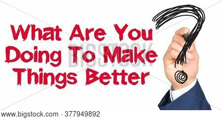 Hand With Marker Writing: What Are You Doing To Make Things Better. Hand Of A Businessman With A Mar