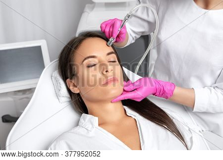 Beautiful Woman With Long Hair, With Clean Fresh Skin.cosmetologist Makes  Procedure Microdermabrasi