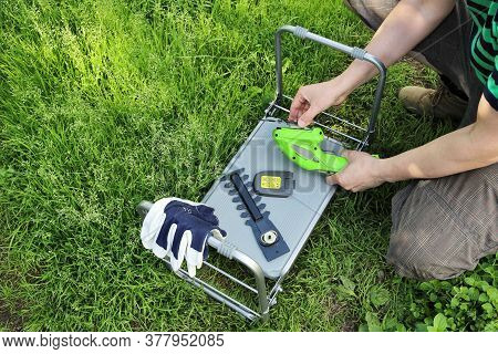 Hands Gather And Disassemble Garden Tools On A Folding Upside-down Table. Changing Cutting Attachmen