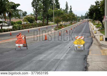 Lake Forest, California / USA - July 23, 2020: City Street being repaved with blacktop. Blacktop is often used for streets and roads.