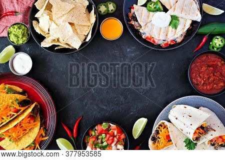 Mexican Food Frame, Above View Over A Dark Slate Background. Tacos, Nachos, Quesadilla And Burritos.