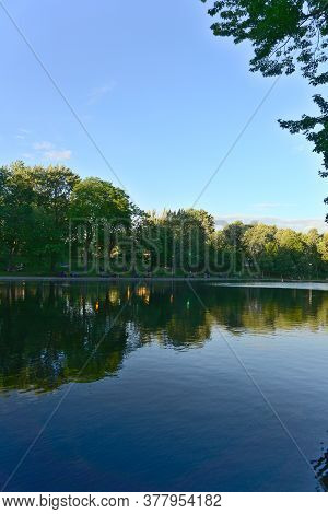 A Vertical Orientation Of Reflections Of Trees And Clouds On Lake Water, La Fontaine Park, Montreal,