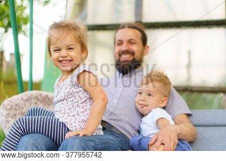 Young Father With Two Small Children Resting In Kindergarten. The Father Spends Time With The Family