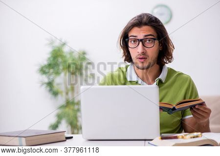 Young male student preparing for exams at home