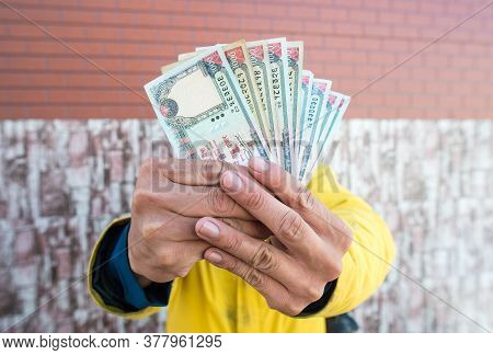 Man Showing A Pile Of Nepalese Money (thousand Rupees Banknotes).