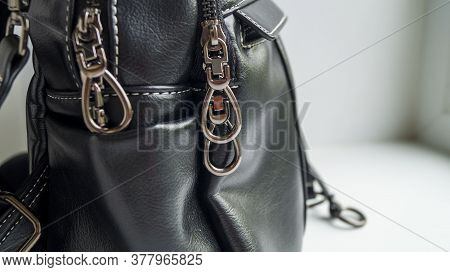 Locks On A Womans Bag. Black Bag On A Light Background. An Accessory For A Fashionable Look. Womens