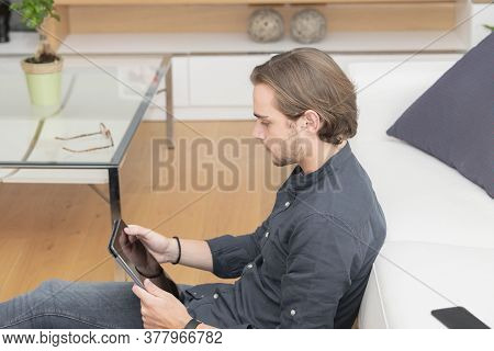 Handsome Young Man Sitting At A Sofa With His Feet On A Table Checking His Phone On A Light Backgrou