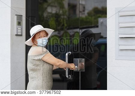 Mature Asian Woman Wearing A Surgical Mask And A Hat Grabbing A Door Handle. Safety And Lifestyle Co