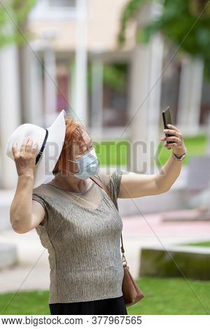 Asian Woman Using A Surgical Mask And Holding A Hat Taking A Photo Of Herself With A Phone