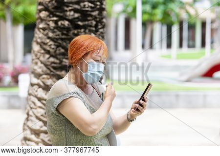 Mature Asian Woman Wearing A Surgical Mask Checking Her Phone Outdoors. Safety And Communication Con