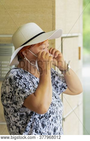 Mature Asian Woman Wearing A Hat Fixing Her Face Mask . Safety And Lifestyle Concept.