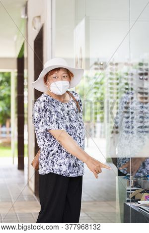 Asian Woman Wearing A Hat And A Face Mask Pointing At Something Behind A Glass Window . Shopping Con
