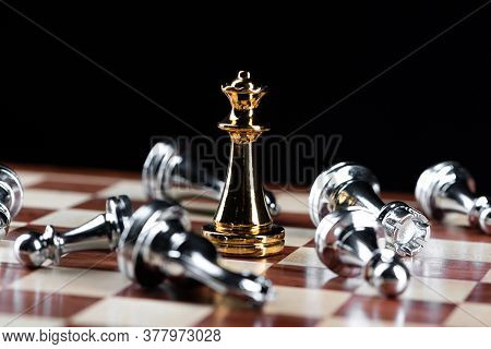 Gold Queen Chess Defeats Silver Figures On Wooden Chessboard. Intellectual Duel And Tactical Battle