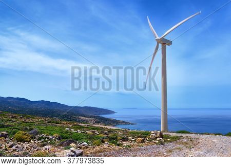 Single Windmill Turbine On Hilltop Of Seashore In Colorful Landscape Against Dynamic Blue Sky With C