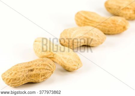 Some Dried And Closed Peanuts Isolated On White Background With Copy Space