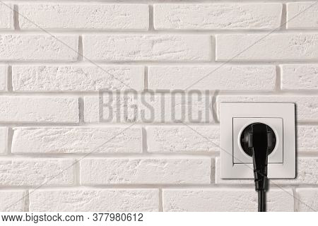 White Brick Wall With Power Socket And Inserted Plug, Space For Text. Electrical Supply