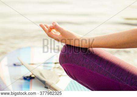 Young Woman Doing Yoga On Sup Board