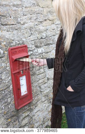 A Woman Posts A Letter In A Post Box In The Uk, Taken 28th Of October 2008 In Witney, Oxfordshire In