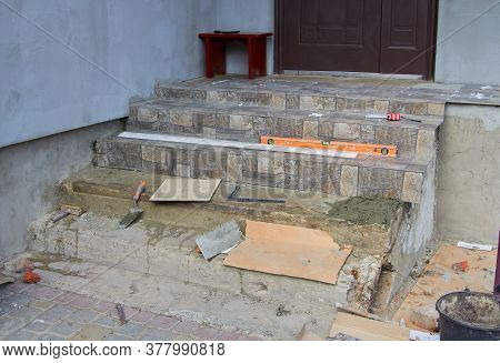 Repair Of Concrete Stairs, Put On The Stairs Gray Tiles, Tools On The Stairs