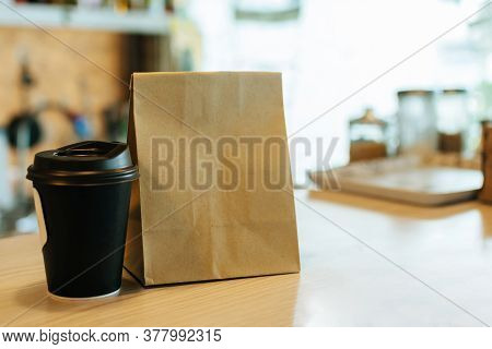 Hot Black Coffee Cup And Dessert Paper Bag Waiting For Customer On Counter In Modern Cafe Coffee Sho