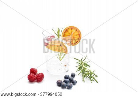Gin And Tonic In A Glass With Orange, Rosemary, Blueberries And Raspberries. Concept Celebration, Pa