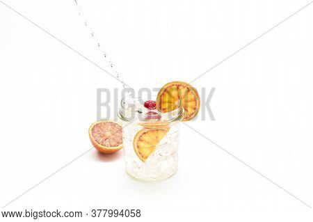 Gin And Tonic In A Glass Jar With Orange And Raspberries. Concept Celebration, Party. White Backgrou