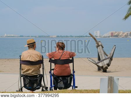 Senior Couple Spending Time Together On The Promenade In The Sunny Day On Blue Sea Background. Elder