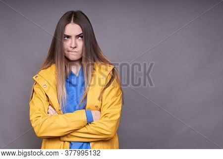 An Angry Young Girl, Dressed In A Yellow Raincoat, Clasped Her Hands On Her Chest, Looks To The Side