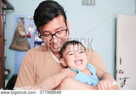 An Infant Toddler Baby Boy Smiling On Fathers Lap
