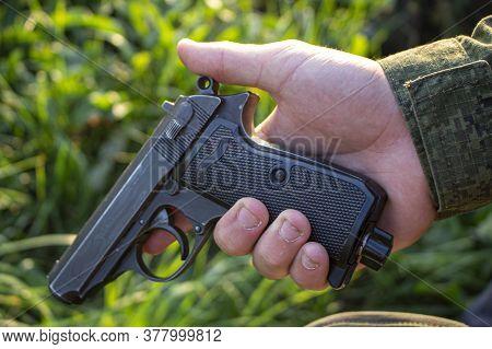 A Gun In A Mans Hand. Training Weapon. Military Training. Shooting Training. The Black Gun Is Cocked