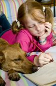 Schoolgirl is making homework together with her dog poster