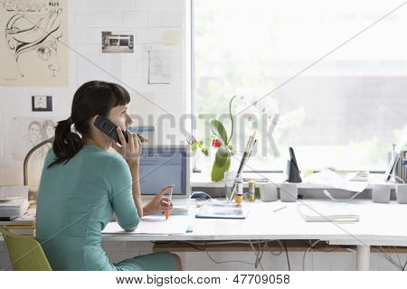 Young female artist using cell phone at desk