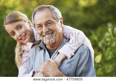 Portrait of young girl embracing grandfather from behind in backyard