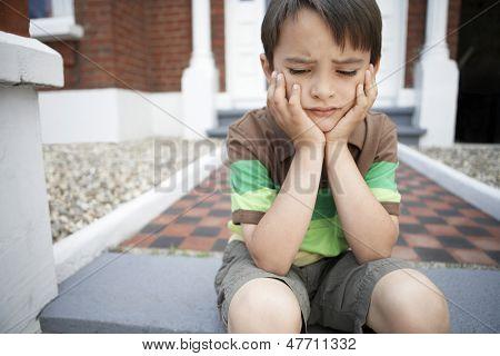 Traurig kleiner Junge mit Händen am Kinn sitzen am vorderen Schritte des Hauses