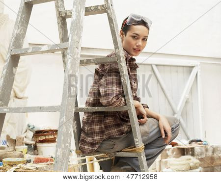 Portrait of young female interior decorator sitting on ladder in work site
