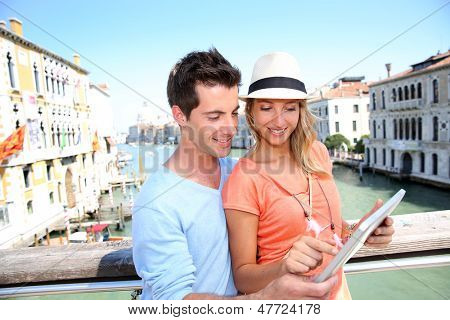 Couple using tablet on the Academia Bridge in Venice, Italy