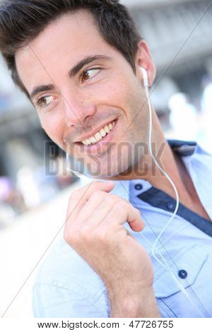 Smiling handsome guy talking on the phone with handsfree