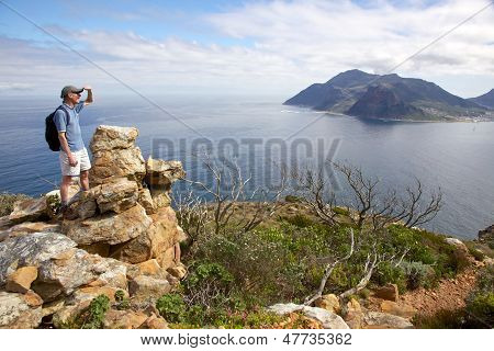 A hiker pauses along the Chapman's Peak section of the Hoerikwaggo Trail in Table Mountain National Park, South Africa, with The Sentinel in the background. poster