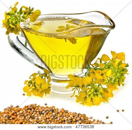 Flower Oil  in gravy boat and mustard flower isolated on white background