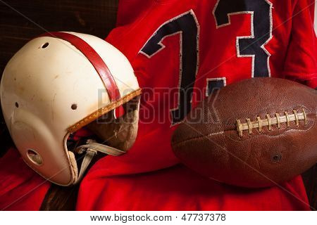 A grouping of vintage, antique american football items including an helmet, jersey, and old leather football