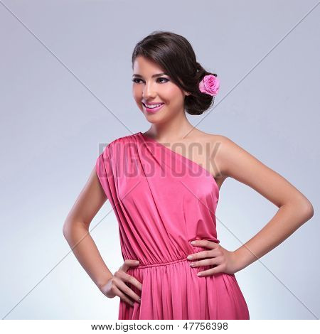 young beauty woman looking away while posing with her hands on her hips and a smile on her face. on a light gray background