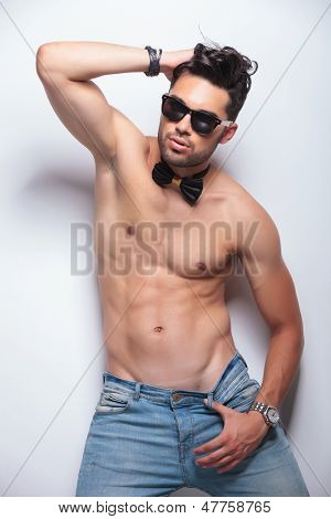 sexy young topless man posing with a hand through his hair and the other on the loop of his pants. on gray background