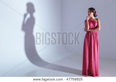 full length photo of a young beauty woman holding her hand at her chin and pensively looking at the camera. on a light gray background with shadow