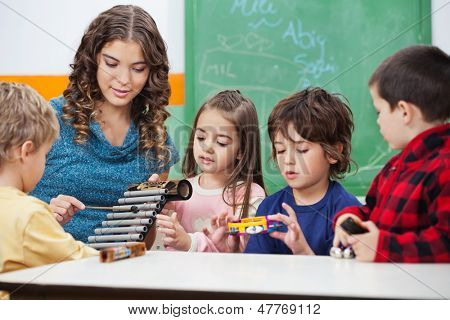 Beautiful preschool teacher teaching students to play xylophone in class