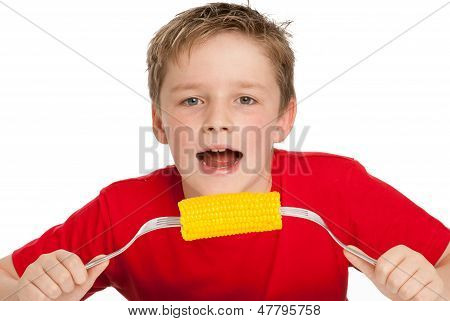 Handsome Young Boy Eating Corn On The Cob.